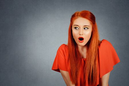 A shocked young redhead woman wearing red dress and yellow makeup looks to the right side down, has a new idea, or has seen something interesting, a red background Banco de Imagens