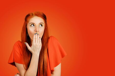 Shocked or surprised young redhead woman wearing red dress and yellow makeup with a hand on the face expressing a wow looking up to the side isolated on a red background