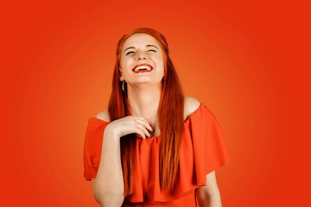 Beautiful young woman with red hair has a lots of fun, isolated on Red background. Redhead girl laughing.