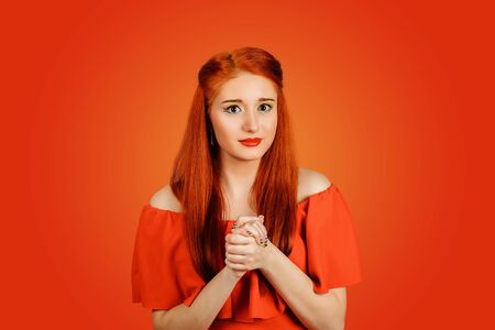 A young young redhead woman wearing red dress and yellow makeup holds his hands as if in prayer isolated on Red background