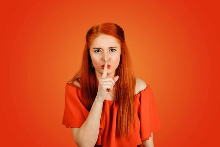 Hush, silence gesture. closeup of young redhead woman in red dress holding placing finger on lips isolated on red  background
