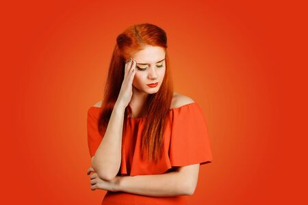 Portrait closeup sad young redhead woman wearing red dress and yellow makeup with worried stressed face expression isolated on red background. Obsessive compulsive, adhd, anxiety disorders