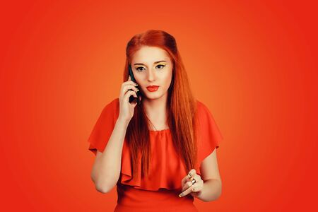 Phone conversation. Beautiful attractive girl redhead woman talking on cellphone in red dress isolated on red background wall. worried, interested face expression emotion body language