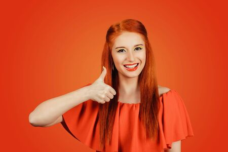 Happy young caucasian female, young woman wearing a red dress with red lipstick, redhead hair making thumbs-up sign smiling cheerfully, showing her support and respect to someone on a red background Banco de Imagens - 134210744