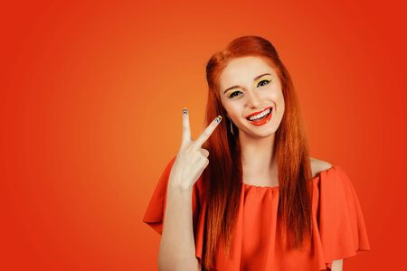 Portrait closeup of Smiling redhead woman in red dress showing victory or peace, two sign isolated on red wall background Banco de Imagens