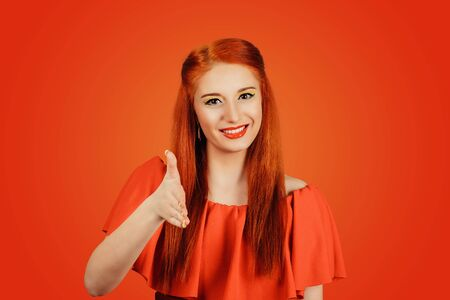 Portrait closeup of a redhead woman in a red dress stretches her hand to meet someone, giving a handshake isolated on a red background. Banco de Imagens