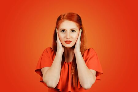 I do not want to hear anything. Closeup portrait attractive redhead young woman covering ears avoiding unpleasant rude situation isolated red background. Hear no evil concept. Neutral face expression Banco de Imagens - 134210763