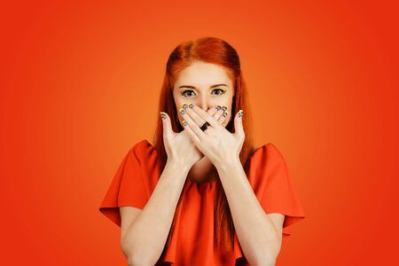 Woman holds her hands on her mouth, covering it, she shows you have to be discreet and keep the silence isolated on red background. Redhead girl covering mouth with hands and staring at camera.