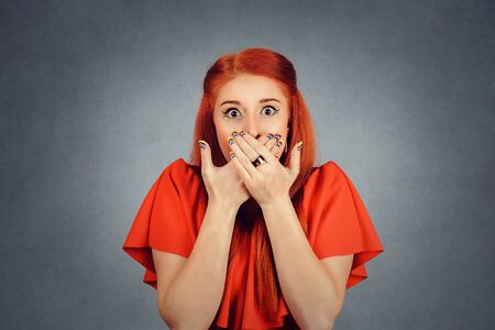 Woman holds her hands on mouth, covering it, eyes wide open in frustration isolated red background. Redhead girl covering mouth with hands and staring at camera. Censorship, freedom of speech concept Banco de Imagens