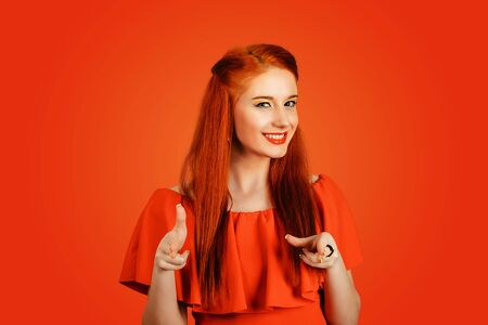 Hey you! Woman redhead young woman pretty girl pointing at camera, point index fingers hands like guns gesture isolated on red background. Emotion face expression.