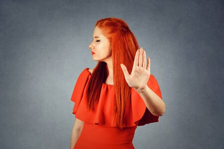 Redhead woman showing Stop, No gesture with hand on grey background