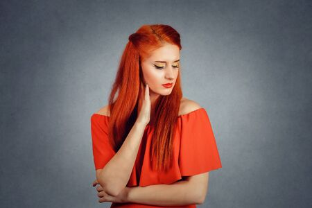 Depressed. Side profile of sad young redhead woman in red dress looking down with eyes closed isolated on grey background