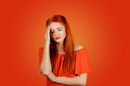Young redhead sad upset stressed woman having headache feeling pain, touching head wearing red dress isolated on a red background feeling desperate on red background