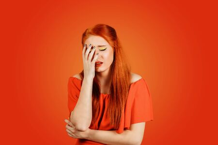 Stressed redhead woman about to cry, depressed wearing red dress with long ginger hair isolated on red background Banco de Imagens - 134594856