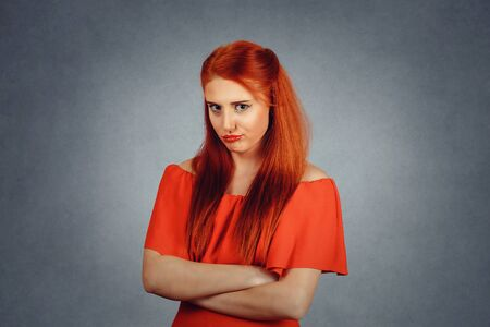 Upset pissed woman looking at you, camera. Young redhead lady wearing red dress and yellow makeup isolated on grey background