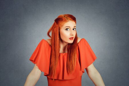 Confused young redhead woman looking at you camera, shrugging shoulders. Young redhead lady wearing red dress and yellow makeup isolated on Red background