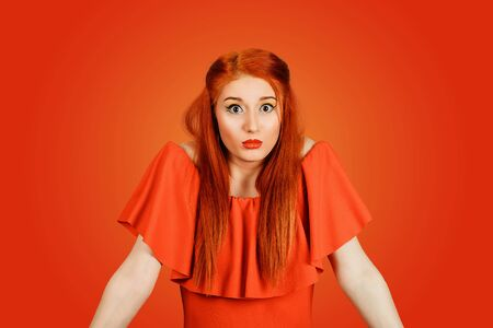 Confused guilty looking woman shrugging shoulders in confusion. Young redhead lady wearing red dress and yellow makeup isolated on Red background