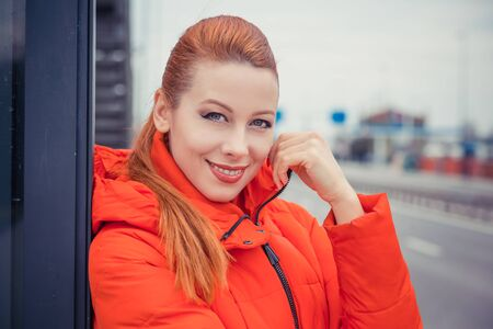 Portrait closeup of a beautiful young redhead woman standing near a road posing girl smiling. Young redhead lady wearing red coat standing outside, outdoors in autumn, winter. City scenery, urban background. Banco de Imagens