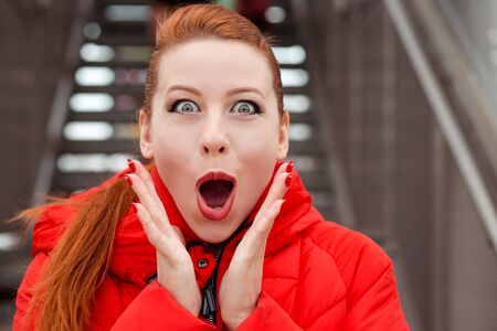 Wow. Close up portrait happy young woman beautiful girl looking excited holding her mouth opened hands up near cheeks Young redhead wearing red coat standing outdoors in autumn winter urban background Banco de Imagens