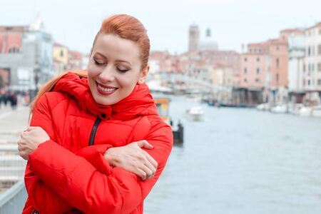 Closeup portrait confident smiling woman holding hugging herself. Young redhead lady wearing red coat standing outside, outdoors in autumn, winter. City scenery, urban background. Banco de Imagens