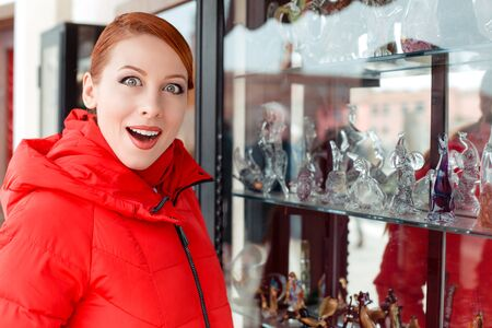 Shocked, amazed stunned young woman looking shocked at a souvenir shop vitrine window in Italy Murano Island. Lady in red winter coat clothing redhead hair Amazing murano glass figurines on background Banco de Imagens