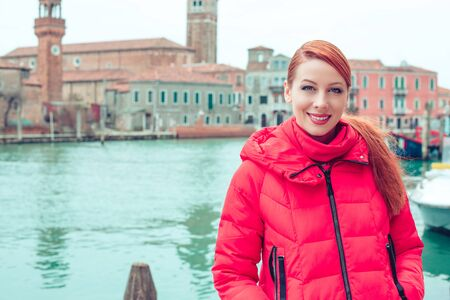 Young woman dressed in red winter coat smiling liner or ferry and sea on the background. Happy traveler, tourist in Venice.