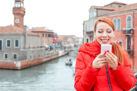 Receiving great news at Carnival in Venice, Italy. Happy young redhead woman tourist in red coat texting at a cell phone in the front of Grand Canal Banco de Imagens