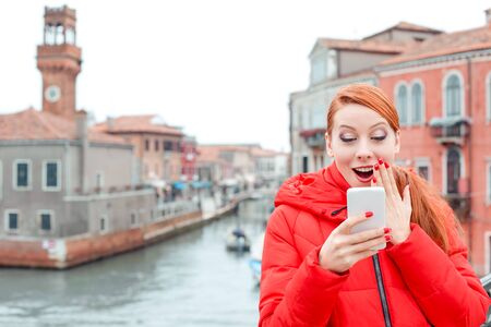 Amazed woman receiving shocking news on a smart phone on the street. Irish model in red winter coat clothing, redhead hair standing on urban background Banco de Imagens