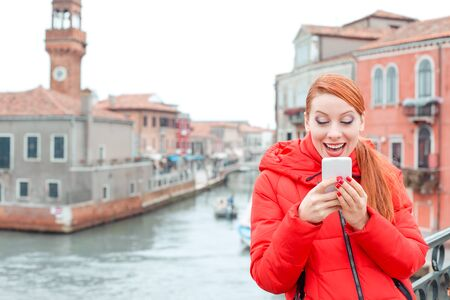 Receiving great news at Carnival in Venice, Italy. Excited, euphoric young redhead woman tourist in red coat texting at a cell phone in the front of Grand Canal Banco de Imagens