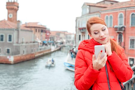 Portrait serious skeptical, worried, displeased young woman reading bad news on smart phone holding using mobile. Lady in red winter coat, redhead hair standing on Venice background near Grand Canal