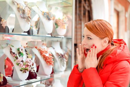 Shocked, amazed stunned young woman in side profile looking at a souvenir shop vitrine window in Italy Murano Island. Lady in red winter coat redhead hair. Amazing murano glass figurines on background Banco de Imagens