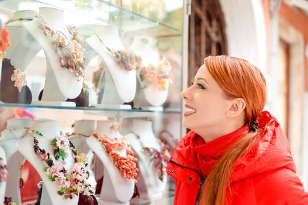 Side profile woman smiling looking at bijouterie in the shop window in Italy Murano Island. Lady in red winter coat clothing redhead hair standing on urban background. Big choice of jewelry concept