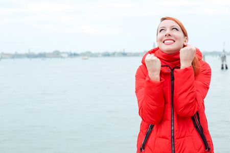 Happy redhead woman in red coat pumping fists in Venice looking up euphoric and happy waterfront, sea on the background in the winter. Happy tourist celebrating her travel Banco de Imagens