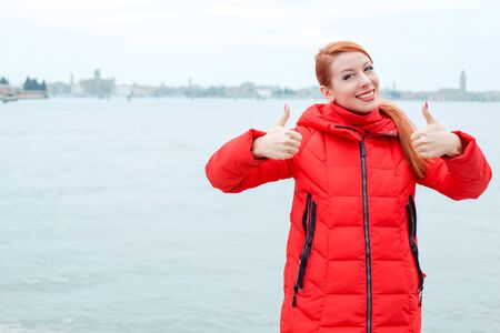 Woman outdoors showing like thumbs up gesture with both hands. Young redhead lady wearing red coat standing outside, outdoors in autumn, winter. City scenery, urban background. Banco de Imagens