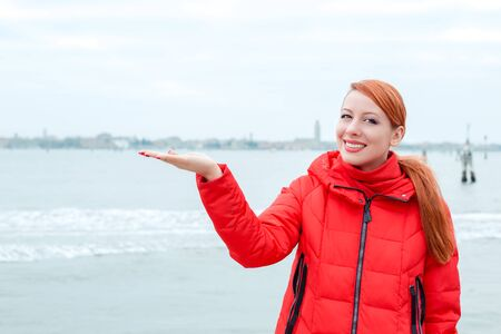 Young woman dressed in red winter coat smiling showing with open palm the sea on the background. Happy traveler, tourist in Venice.
