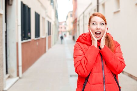 Deal or sale, shocking news. Shocked woman in Murano, Venice, Italy. Irish model in red winter coat clothing, redhead hair standing on urban background. Amazed, stunned, emotion, expression concept. Banco de Imagens