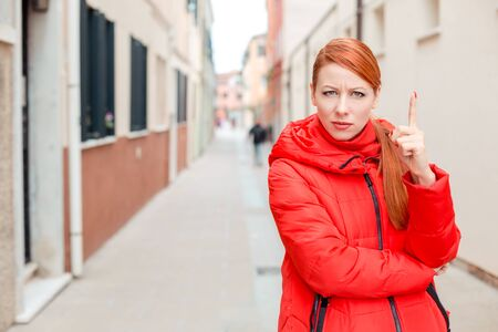 Attention, listen to me. Close up portrait of young woman wagging her finger raised. Young redhead lady wearing red coat standing outside, outdoors in autumn, winter. City scenery, urban background. Banco de Imagens