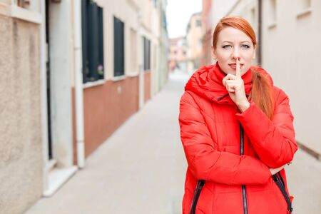 Closeup portrait of a beautiful angry woman showing hush silence hand gesture with index finger on mouth. Young redhead lady wearing red coat standing outside, outdoors in autumn, winter. City scenery, urban background.