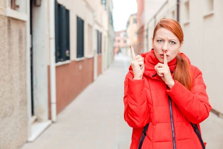 SHH. Angry woman showing shh, silence, hush sign gesture with one hand and attention listen to me with other. Young redhead lady wearing red coat standing outside, outdoors in autumn, winter. City scenery, urban background.
