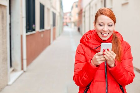 Professional business woman on smartphone smiling happy wearing red coat outwear. Young happy casual woman texting on smart phone walking outdoor in fall or winter on a Italian street. Caucasian model Banco de Imagens - 134203452