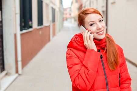 Professional business woman on smartphone smiling happy wearing red coat outwear. Young happy casual woman talking on smart phone walking outdoor in fall or winter on a Italian street. Caucasian model