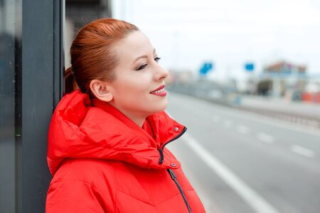 Redhead woman smiling looking to the side wards daydreaming, thinking relaxing, enjoying life in the city road on urban background. Young female in red coat winter clothing Banco de Imagens - 134203454