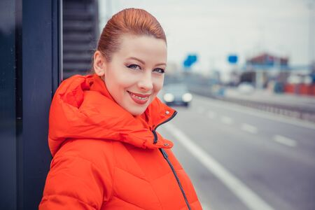 Happy young adult woman smiling with teeth smile outdoors and standing at bus station on city street near a road at sunset time wearing winter clothes