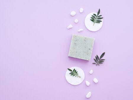 Fresh green leaves on cotton pads, natural cosmetics, handmade soap and salt stones isolated on a purple background. Flat lay, top view, copy space