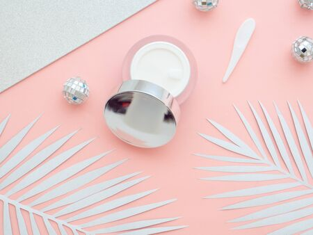 Your moisturizer cream for holidays. Makeup cosmetics, cream bottle container and Christmas balls isolated on pink, peach color copy space background with white fern leaves on it. Top view