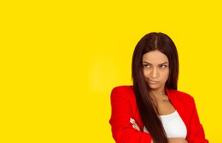 Displeased suspicious, jealous or envious young woman looking sideways. Negative face expression emotion perception. Mixed race model isolated on yellow background with copy space. Natural, no makeup.