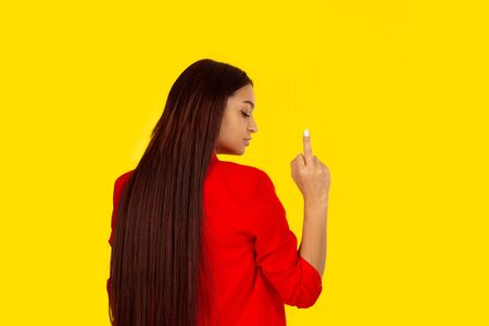 Multicultural woman with her back turned towards the camera is showing you with middle finger. Mixed race model isolated on yellow background with copy space. Horizontal image. Natural, no makeup