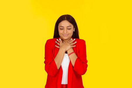 Thankful. Woman holding hands on her chest showing her pleased attitude. Mixed race model isolated on yellow background with copy space. Horizontal image. Natural, no makeup.
