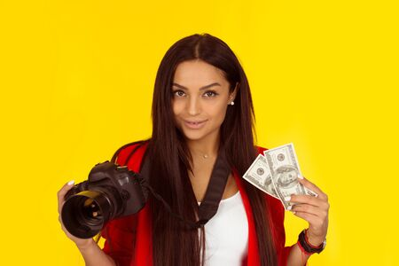 Woman holding profesional photo camera and USA dollars cash money currency. Mixed race model isolated on yellow background with copy space. Horizontal image. Natural, no makeup.