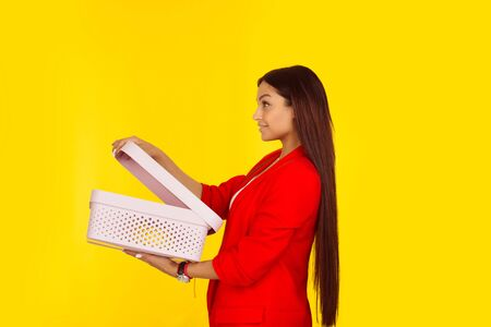 Side profile of a woman holding an open box. Mixed race model isolated on yellow background with copy space. Horizontal image. Natural, no makeup.